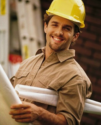 Smiling Contractor At Worksite Holding Blueprints
